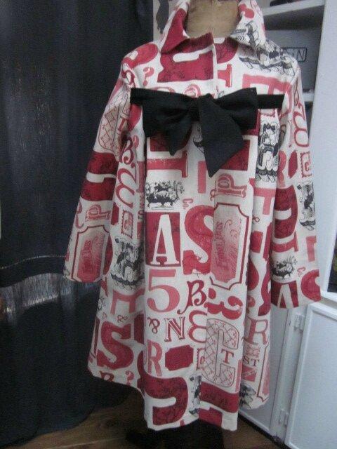 """Un manteau AGLAE en toile de coton imprimé """"caractères d'imprimerie"""" rouge et noir fermé par un noeud de lin noir..."""