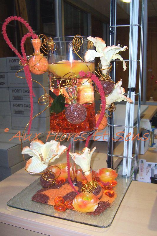 Composition fleurs artificielles, bougies et sables orangés