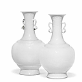 A very rare pair of imperial white-glazed relief-carved bottle vases, qianlong seal marks and of the period (1736-1795)