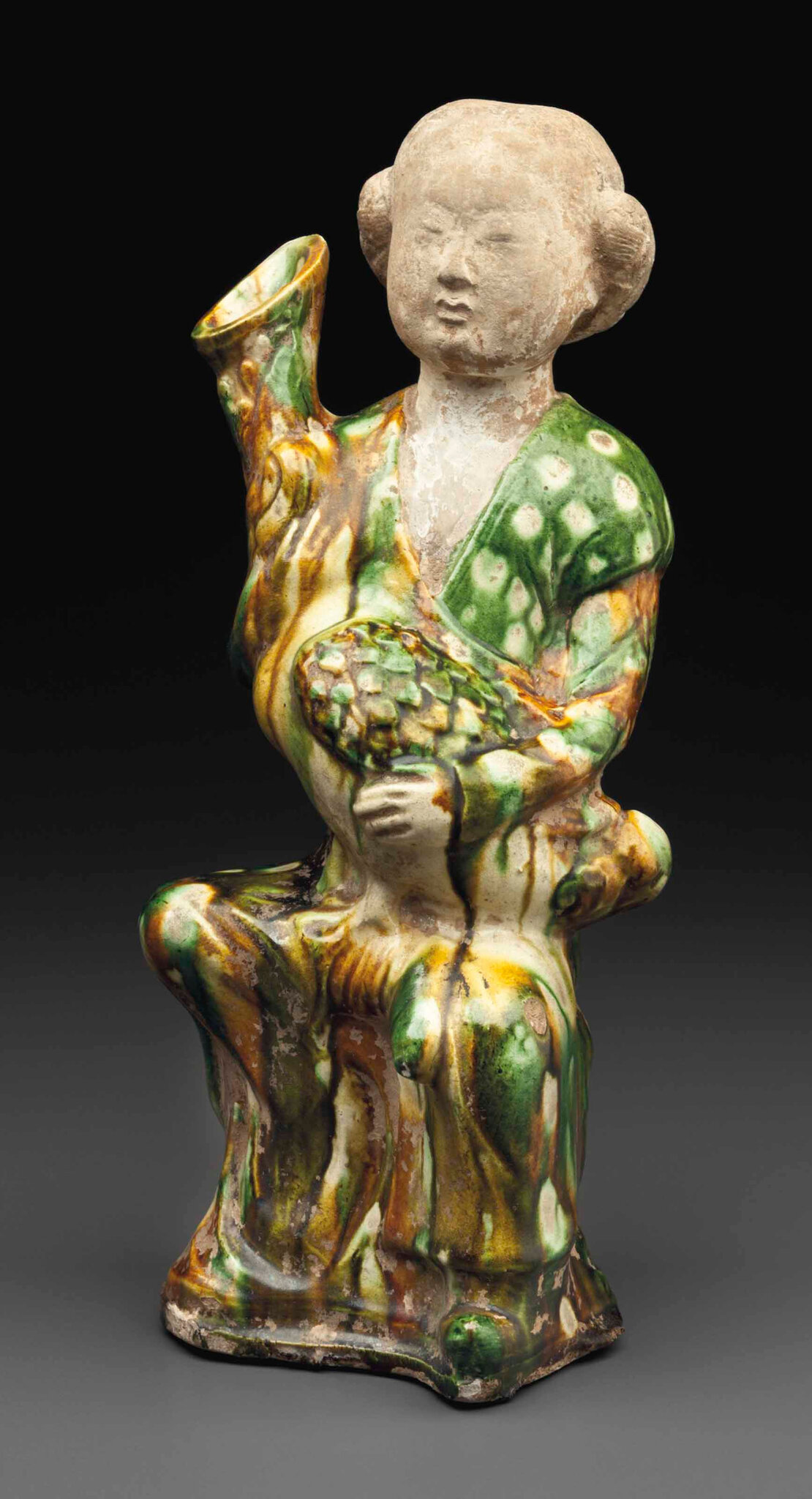 A sancai-glazed figure of a woman holding a goose, Tang dynasty (AD 618-907)