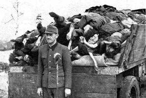 SS man Hoessler posing with the corpses during his arrest in 1945