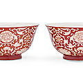 A pair of coral-ground reserve-decorated 'lotus' bowls, qianlong underglaze blue seal marks and of the period (1736-1795))