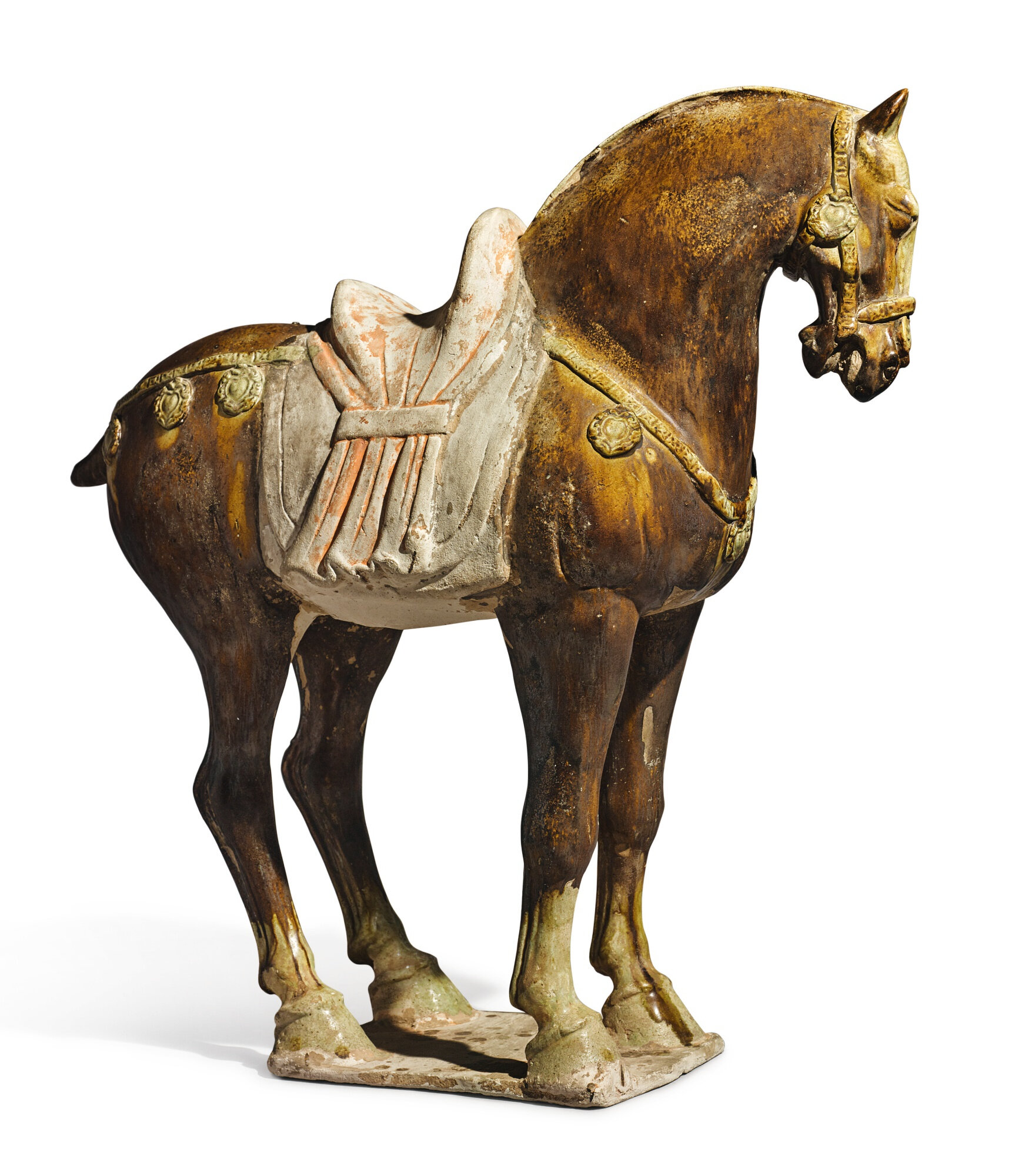 An amber-glazed pottery figure of a caparisoned horse, Tang dynasty (618-907)