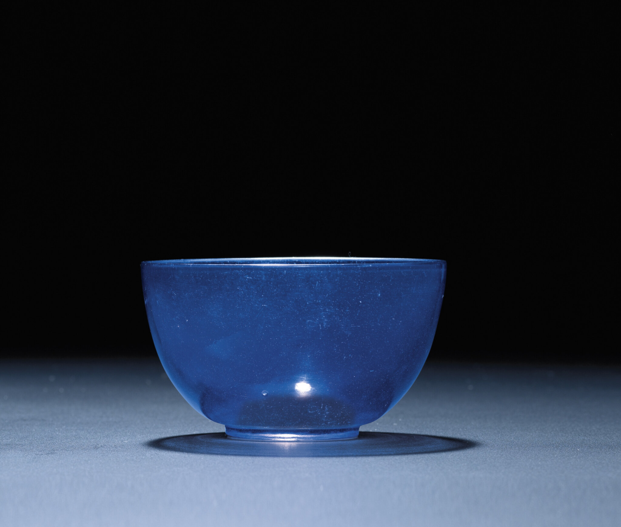 An unusual imperial transparent blue glass bowl, Qianlong incised four-character mark within a square and of the period (1736-1795)