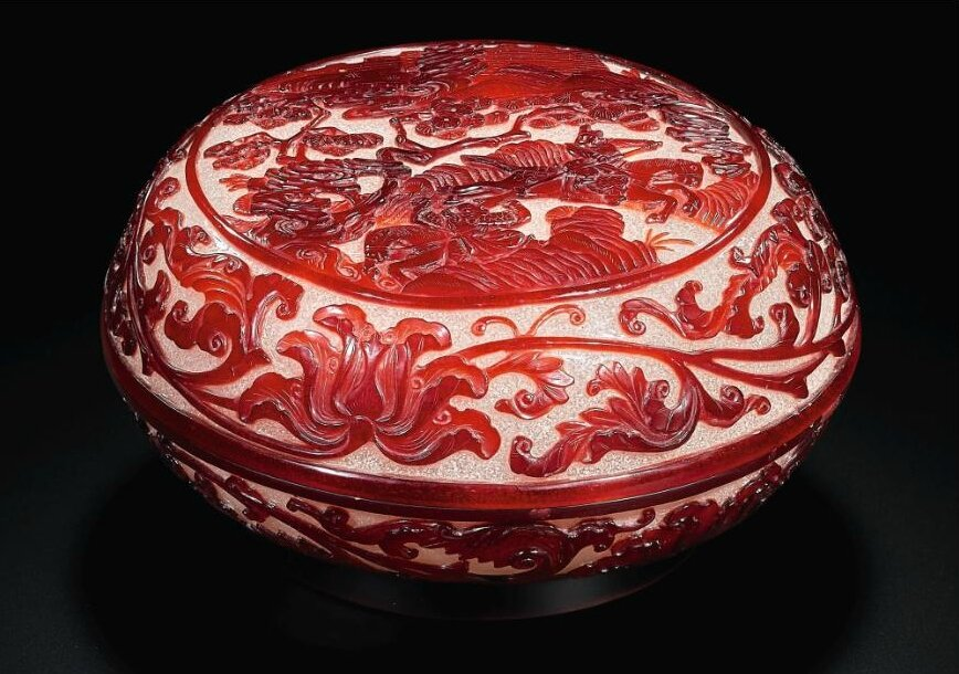 A finely carved imperial ruby-red overlay glass 'warriors' box and cover, Qing dynasty, Qianlong period (1736-1795)
