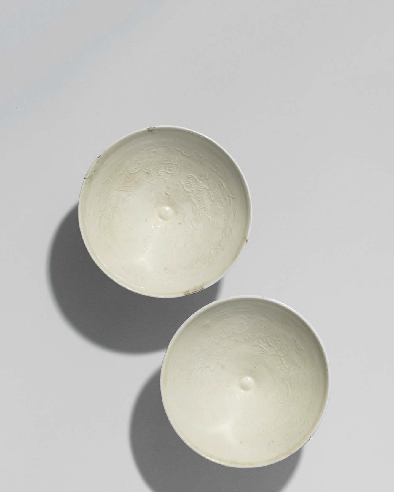 A pair of Huozhou white-glazed moulded 'Peony scroll' bowls, Jin-Yuan dynasty (1115-1368)