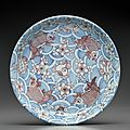 A large and unusual underglaze-blue and copper-red-decorated dish, Kangxi six-character mark in underglaze blue within a double circle and of the period (1662-1722)