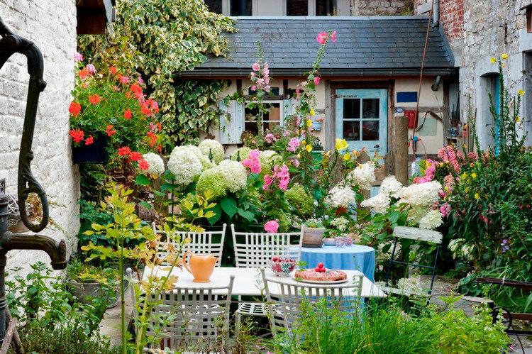 aménagement-cour-intérieure-table-chaises-blanches-hortensias-petunias