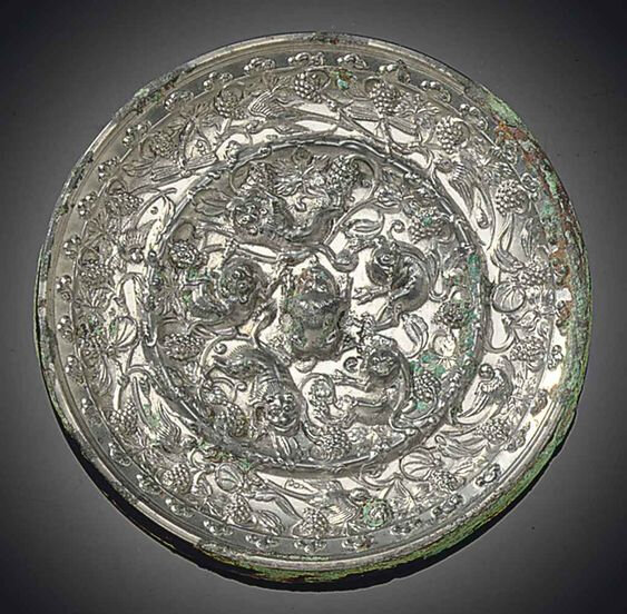 A silvery bronze 'Lion and Grapewine' circular mirror, Tang dynasty (618-907)