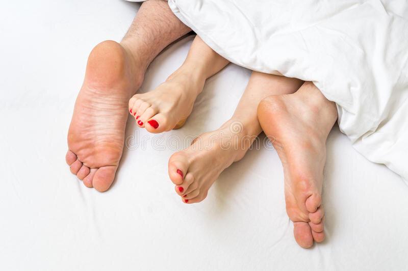 pieds-d-un-couple-dans-le-lit-sous-la-couverture-87837413