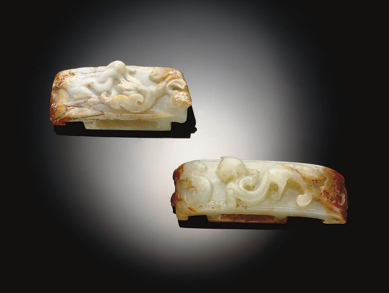 Two greenish-white and russet jade scabbard slides, Han dynasty, 2nd-1st century BC