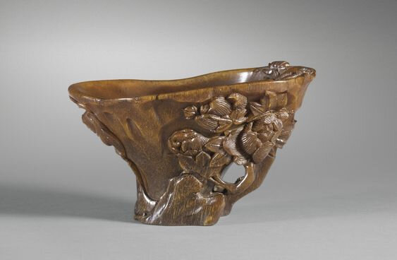 A carved rhinoceros horn 'lingzhi and peonies' libation cup, China, Qing Dynasty, 17th century