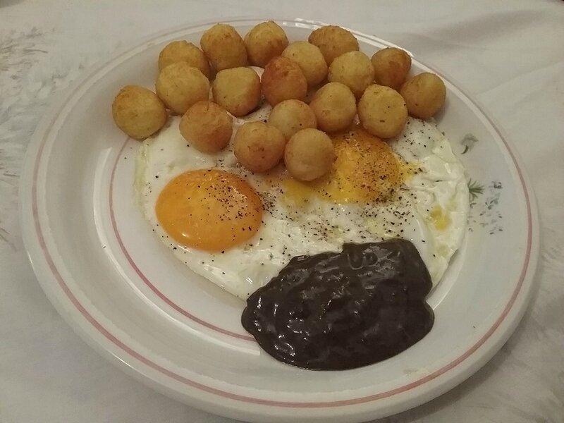 Œufs sur le plat et pommes dauphines à la crème d'ail noir