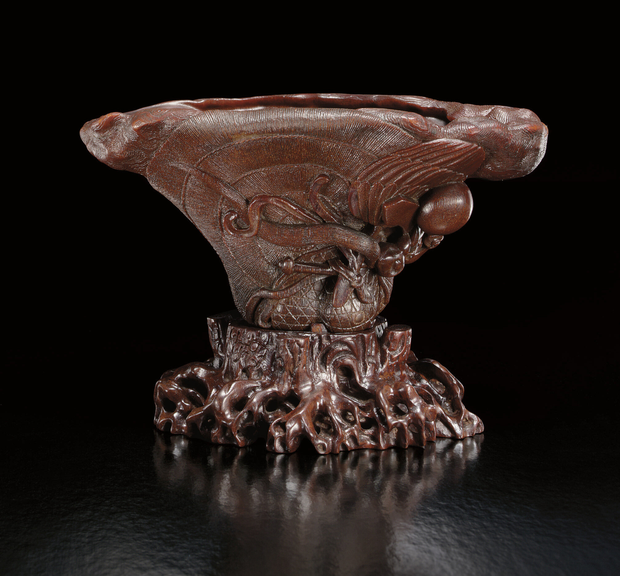 An extremely rare and finely carved rhinoceros horn 'Wood grain and an baxian' libation cup, Ming dynasty, 17th century