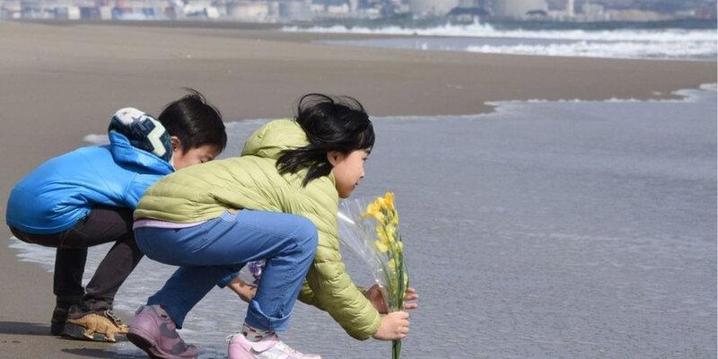 deux-enfants-deposent-des-fleurs-dans-la-mer-en-hommage-aux-victimes-de-fukushima-non-loin-de-la-centrale-nucleaire-de-sendai-en-arriere-pla