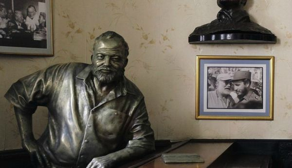 653458_a-life-size-bronze-statue-of-u-s-writer-ernest-hemingway-at-his-regular-spot-at-the-floridita-bar-stands-beside-a-picture-of-former-leader-fidel-castro-and-the-writer-taken-when-they-met-at-a-f