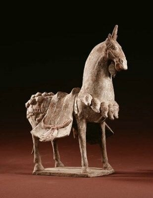 A painted buff pottery figure of a caparisoned horse, Northern Wei Dynasty (386-534)