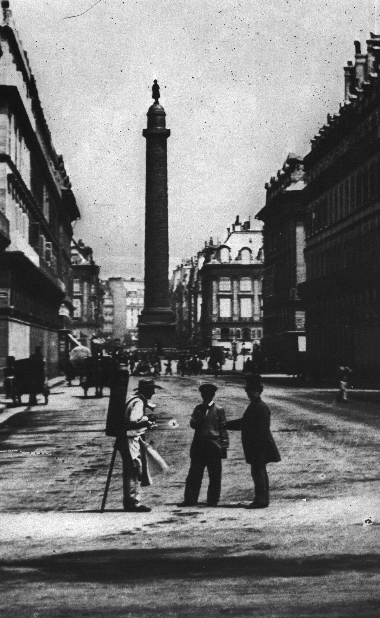 1852-1870 Un vendeur de coco, rue de Castiglione, la colonne Vendôme est surmonté de Napoléon Ier en Redingote
