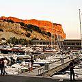 Cassis - Le port et la grande falaise, dorée par le soleil couchant