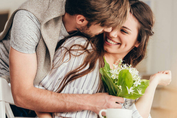 depositphotos_156649708-stock-photo-young-couple-embracing-with-bouquet