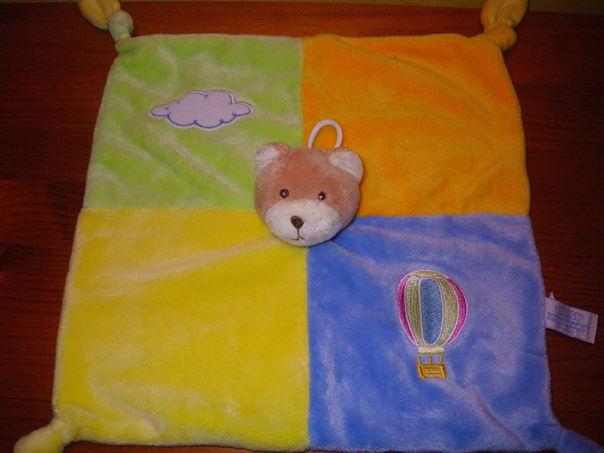 ours marque Gipsy, doudou plat 27 cm, composé de 4 carrés de couleurs diff, motif brodé mongolfière